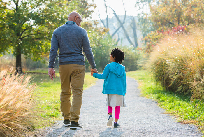 Grandfather and granddaughter walk in the park
