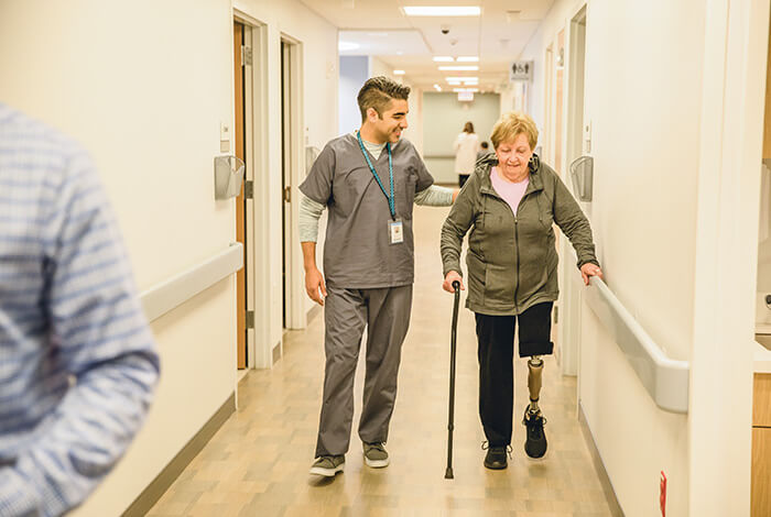 physician walking member down hospital hallway