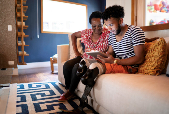 A man with prosthetic legs and his mother using a tablet while sitting on couch