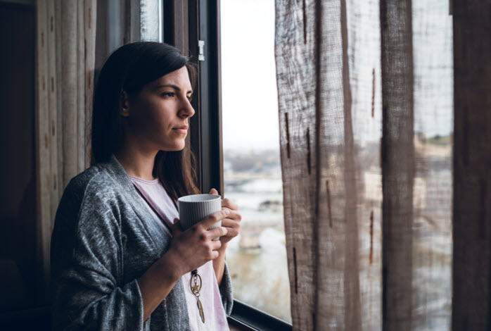 woman looks out window while holding mug