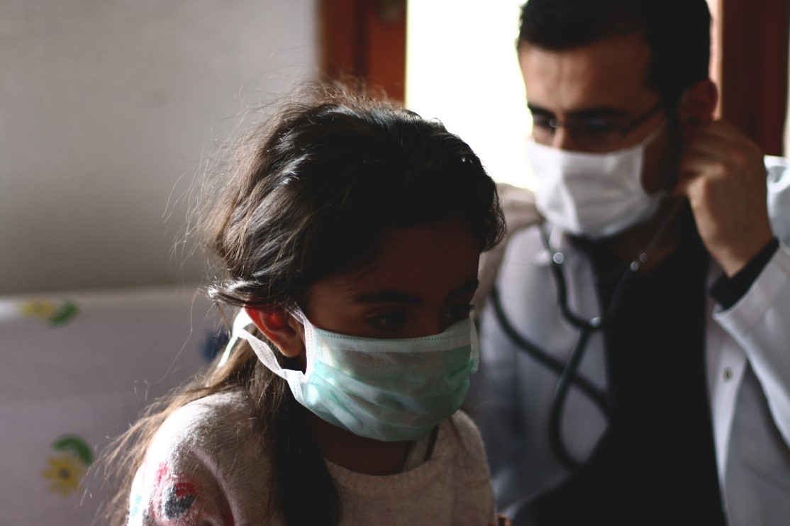 young girl patient and doctor wearing masks during a checkup